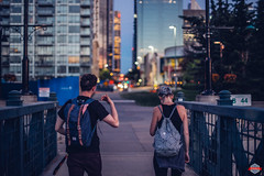 Evening Stroll (Rob Moses) Tags: calgary alberta canada yyc city urban metro downtown buildings architecture citylife modern streetphotography people man guy dude girl woman walking bokeh canon 50mm 12 sony a7ii canonfd vintage old classic legacy bridge