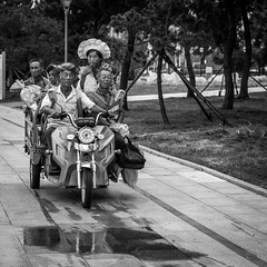All together (Go-tea ) Tags: canon eos 100d 50mm street city hurban qingdao huangdao outside outdoor bw bnw blackwhite blackandwhithe black white asia asian china chinese weat dry puddle water poeple motorbyke loaded over seated standed havy bagds travel passengers driver driving road trip relatives men woman hat young old life portrait