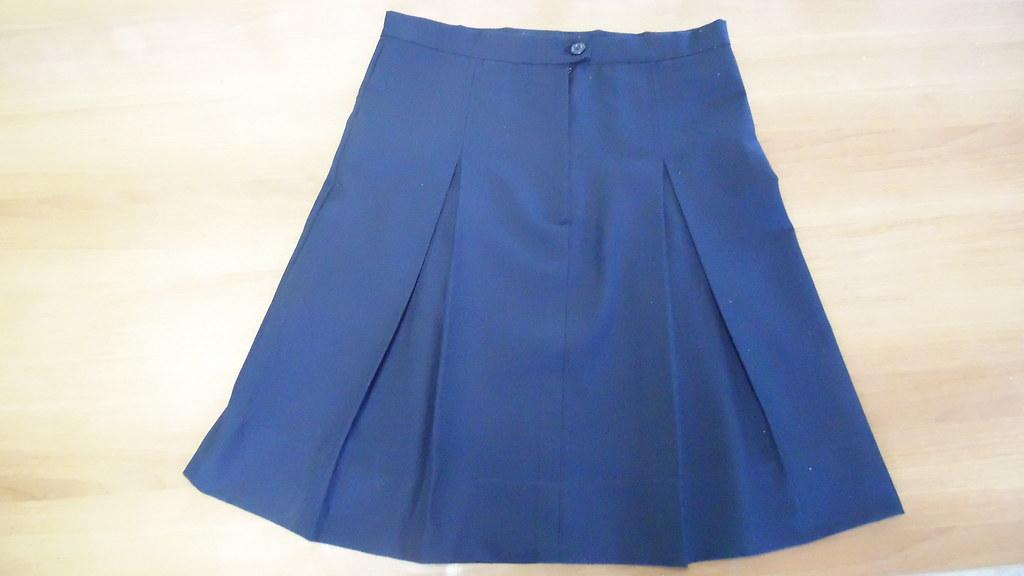Falda azul marino, con dos tablas encontradas frontales  y traseras. Largo hasta cuatro dedos horizontales sobre la rodilla. Terminación cierre y botón.
