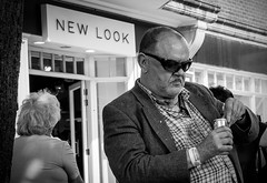 A New Look (The Image Den) Tags: man sign expression candid drinking streetphotography canterbury sneer newlook wristband bloke xt1