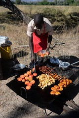 10075458 (wolfgangkaehler) Tags: africa travel people cooking breakfast tomato person bacon potatoes bush african sausage safari potato zambia chefs fritters southernafrica 2016 zambian southluangwanationalpark