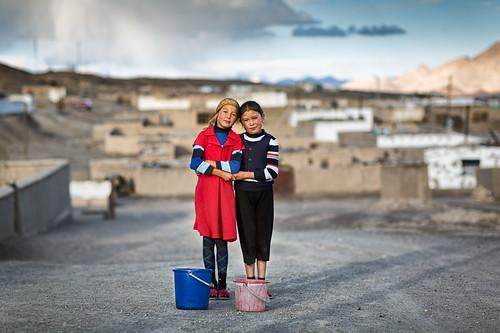 Two Kyrgyz girls standing in a street in Murgab, Tajikistan