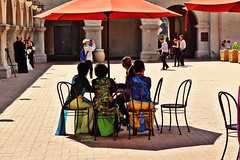 The Council of Elders (Art By Pem Photography: Tao Of The Wandering Eye) Tags: fineartphotography canon canoneosrebelsl1 eos sl1 weddingparty wedding elders outdoor scenicsnotjustlandscapes people pattern color colour colors colours courtyard fancy women men pavement candid usa travel southerncalifornia umbrella umbrellas shadow shadows light sunlight