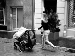 Suffocating mother love (Giangaleazzo) Tags: street city west monochrome wheel canon germany hair bag children eos bonn strada doors child stroller walk mother son run via mum mamma trousers hurry borsa nylon madre passeggino germania suffocate citt ruota fretta correre 40d