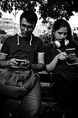 A Modern Kind of Dating (stimpsonjake) Tags: nikoncoolpixa 185mm streetphotography bucharest romania city candid blackandwhite bw monochrome young youth boyfriend girlfriend smartphone dating modern technology love romance couple