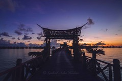 Sunrise at Mabul Island. (Syahrel Azha Hashim) Tags: morning travel bridge light vacation holiday detail colors beautiful silhouette architecture clouds sunrise island nikon colorful dof getaway details horizon naturallight nobody nopeople resort tokina malaysia handheld shallow simple dramaticsky 11mm woodenbridge sabah leadinglines ultrawideangle colorimage mabulisland d300s syahrel