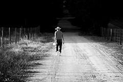 the walk back to the ranch (joaobambu) Tags: road brazil blackandwhite bw man topv111 brasil rural fence walking countryside interestingness interesting poetry poem walk pb elderly blogged antonio pretoebranco echaporã sashi estradasbiz