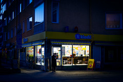 Streets (Toni Ahvenainen) Tags: loxia250 mediumaperture darkness street kiosk man lighting cigarette bluelight bluehour zeiss