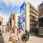 Louvain-La-Neuve - Rue des Wallons - 'Qu'est-ce qu'un intellectuel ?' (Roger Somville) - '24 heures vélo' (Vincent Rousseau) thumbnail