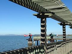 Harbor Art (Melinda Stuart) Tags: biplanes sculpture wood pilings walkway pergola emeryville eastshorepark ca bayarea sfbay eastshore viewing pier tylerhoare water bay