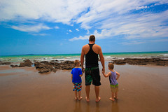 Always safe with dad (WhittneyMareePhotography) Tags: blue sky beach boys water clouds holding dad hand safe oceon