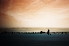 stick man (fotobes) Tags: shadow sea sky man beach silhouette bench sussex lca brighton pavement hove horizon running negativespace analogue seafront jogging runner vignetting railings jogger lomochrometurquoise lomochrometurquoisexr100400