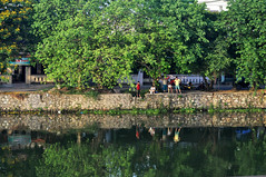 By the river (Roving I) Tags: trees friends water reflections relaxing vietnam rivers leisure stonewalls hue groups