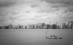 Praia em Guarapari - ES (HebertLopes) Tags: city sea brazil sky blackandwhite bw sun beach monochrome brasil architecture landscape boat nikon cityscape espiritosanto brasilemimagens