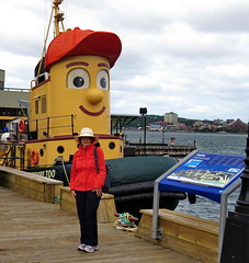 Huguette posing with Theodore Too on the Halifax Boardwalk (Yvon from Ottawa) Tags: television children waterfront harbour tourist boardwalk harbourfront tugboat halifax tours attraction theodore baseballcap theodoretugboat theodoretoo redbaseballcap televisionseries