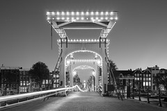 Gateway to Amsterdam (McQuaide Photography) Tags: amsterdam noordholland northholland netherlands nederland holland dutch europe sony a7rii ilce7rm2 alpha mirrorless 1635mm sonyzeiss zeiss variotessar fullframe mcquaidephotography adobe photoshop lightroom tripod manfrotto light licht night nacht nightphotography longexposure stad city capitalcity urban lowlight architecture outdoor outside old oud amstel grachtenpand canalhouse house huis huizen traditional authentic water centrum gebouw building waterside tourism touristattraction travel bridge magerebrug skinnybridge brug blackandwhite bw mono monochrome wideangle groothoek lighttrail