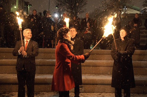 Governor Gina Raimondo lights torches for Lt. Governor Dan Mckee, Treasurer Seth Magaziner, and Attorney General Peter Kilmartin at the 2015 RI Inauguration Celebration. Photo by John Nickerson.
