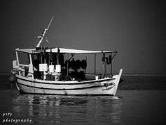 resting in calm sea... (gregtz) Tags: sea blackandwhite bw reflection boat blackwhite seaside fishing greece emotions patras