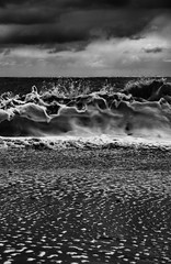 The wave upon the shore (miniwaites) Tags: sea england sky blackandwhite cloud beach water monochrome clouds mono sand moody unitedkingdom stones wave shore foam gb frothy splash foamy textured foaming breaking lightrays thorpeness froth splashing frothing