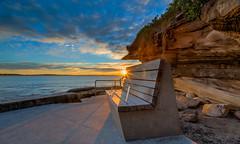 Sunrise by the chair Cronulla Beach Sydney (600tom) Tags: ocean blue sea orange cloud sun beach water sunrise bench rocks shadows vivid australia seafront bushes brackets flair cronulla