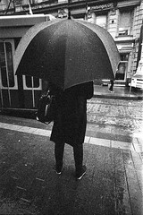 Umbrella series (__ _) Tags: urban blackandwhite rain umbrella 35mm finland helsinki kodak trix grain streetphotography figure lone selfdeveloped filmisnotdead personalproject walkbyshot exxpiredfilm