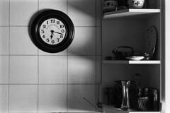 The Day has the Time we Want... (Ninoo Vita) Tags: white black clock kitchen misty photography lights lightsandshadows shadows gloomy kodak trix overcast ishootfilm nikonf100 dim rodinal schwarzweiss somber murky schwarz dingy drab  darkened shadowy weis nocolor monochromia epsonv750 inspirationalphotography blackwhitepassionaward emozioniinbiancoeneroemotionsinblackandwhite yourperspectiveandcreative nikkor11850mmseriesepancake