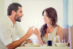 Young romantic couple drink to each other at restaurant (Misc) (hypesol) Tags: two people woman man love glass girl smiling laughing table happy restaurant glasses other girlfriend couple looking wine drink african young romance relationship together dating romantic date talking having each