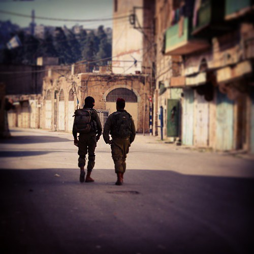 Two #israeli #soldiers walk down #Shuhada street- also known as apartheid street- in #Hebron. This street has been closed for #Palestinians since the American-born Jewish settler Barauch Goldstein massacred 29 Palestinians in the Ibrahimi #mosque whilst t