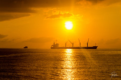 Warm glow of new beginning (Pipo De Jesus) Tags: ocean sunset sea orange sun water silhouette sunrise gold golden boat warm ship peace sunsets atmosphere calm cargo tanker liner 500px