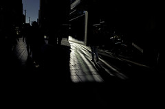 Darkness Creep (Paradise.Found) Tags: life seattle street city light shadow people urban usa sun art strange perception flickr shadows outdoor candid culture streetphotography documentary wideangle bluesky social depthoffield human shade essential environment sight framing unposed society critical ricohgr interference insight reference decisivemoment observer westlakecenter interpretive streetphotographer descriptive paradisefound alienskinexposure streettogs miltongarrisonphotography