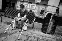 Down On His Luck (nigelhunter) Tags: street urban shop bench bag walking glasses pavement cigarette candid seat smoke down bin e luck stick refuse crutches spectacles let deprivation