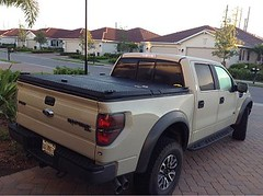 A Black Truck Bed cover on a Ford Raptor (DiamondBack Truck Covers) Tags: ford se aluminum closed c pickuptruck driveway raptor diamondback diamondplate whitetruck ff09 tonneaucover truckbedcover wholetruck passengersidetaillightview ruggedblack