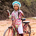girl on bike in traditional costume