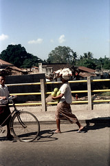 24-628 (ndpa / s. lundeen, archivist) Tags: city people bali woman man color film bike bicycle 35mm buildings indonesia town village sandals candid nick citylife streetphotography pedestrian southpacific balance 24 1970s 1972 balancing indonesian carry carrying balinese dewolf oceania pacificislands nickdewolf photographbynickdewolf onherhead reel24