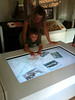 Child using bespoke software on Grand Multi-Touch Table