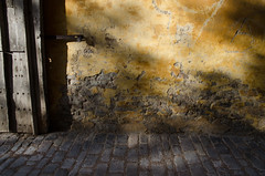 276/365 - A (Spannarama) Tags: door uk yellow wall graffiti wooden carved october gate stones wells somerset plaster cobblestones marketplace 365 padlock textured crumbling 2014 bishopspalace a bishopseye