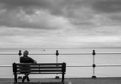 Looking out to sea (All I want for Christmas is a Leica) Tags: panasoniclumixgf6 panasonic lumix 1232mm f35f56 panasoniclumix1232mmf35f56 penarth penarthpromenade bench people monochrome blackwhite outdoor solitaryman waitingforgodot