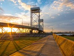 Bridge to the Upper Ninth Ward (rowjimmy76) Tags: road bridge sunset sky clouds canon landscape louisiana neworleans powershot sunflare levee s100 lowerninthward