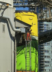 Taking a break (Ruth and Dave) Tags: man tower art vancouver mural industrial factory break watching platform overalls worker giants ladder granvilleisland osgemeos oceancement cementworks vancouverbiennale