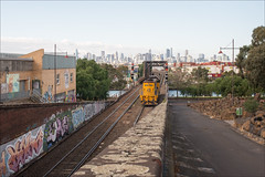 footscray-3258-ps-w (pw-pix) Tags: road street city trees sky cloud brick lines stone skyline train docks river clyde haze waiting rocks steel tracks australia melbourne victoria warehouse signals rails locomotive lichen bigwheel freight containers patina ballast idling sleepers truss footscray westernsuburbs southernstar maribyrnongriver xclass dieselelectric melbourneskyline clydeengineering x54 wheelofmisfortune bunburystreet aurizon bunburystbridge maribyrnongriverrailbridge viewfrombunburystreettunnelentrance