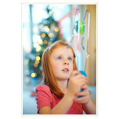 retro xmas (khrawlings) Tags: christmas xmas portrait tree girl wheel toy concentration kid child bokeh candid space retro present 70s slider magnet spinner