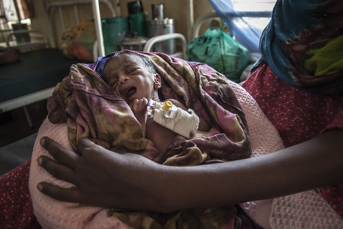 A mother holds her new-born child firmly in Kakuma Refugee Camp, norhtern Kenya