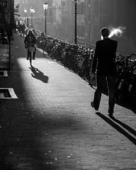 The smoker and the cyclist (S.R.Murphy) Tags: blackandwhite bw sunlight netherlands monochrome amsterdam bike bicycle contrast mono cyclist smoke streetphotography silouette cycle smoker jordaan socialdocumentary urbanlandscape cigarettesmoke canon24105mm canon6d lightroom5 oct2014