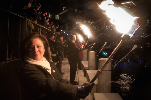 Secretary of State Nellie Gorbea poses with a torch during the WaterFire Lighting Ceremony. Photo by Jen Bonin.