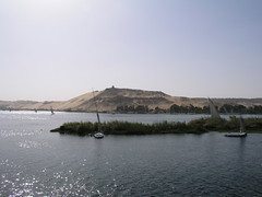 Aswan,  view of Qubbet el-Hawa (dr.heatherleemccarthy) Tags: trees plants sunlight water cemetery sailboat river boat sand afternoon hill egypt nile hillside aswan tombs necropolis