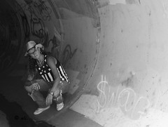 Show some $W@G (Catching_alchemic light) Tags: blackandwhite monochrome portrait self cowboy cowboyhat torn jeans rippedjeans sneakers whiteshoes tunnel graffiti swag show water paint spraypaint stars stripe necklace pose lookingout moneysign