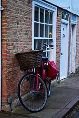 Waiting for a ride (Christina 25) Tags: street cambridge red house building brick window bike bicycle wheel wall bag doors basket ride unitedkingdom whitedoor redbike