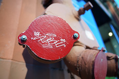 Tiny tag (Eric Flexyourhead (shoulder injury, slow)) Tags: city red urban usa detail oregon portland graffiti sticker downtown tag pipe cover pdx outlet ricohgr standpipe fragment stumptown shallowdepthoffield rosecity urbanfragment multnomahcounty streetfragment