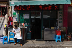 In Front of the Restaurant (pruse) Tags: china street city urban man building writing awning person restaurant store shanghai storefront sit hongkou 570 plasticstool