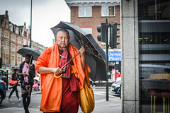 Monk under cover (sara.wendelmelhuish) Tags: summer orange london rain umbrella bag pavement walk monk edgwareroad